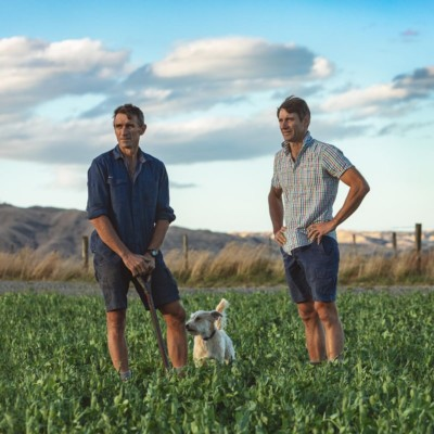 Brothers Andrew and James in farm field with dog looking out across farmland with hills in background