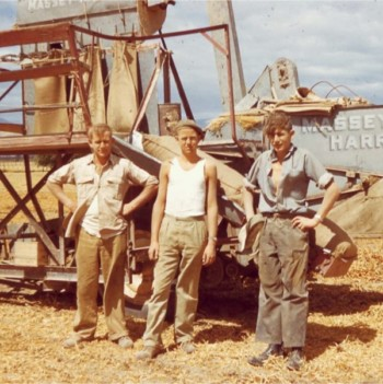 Old photo of father and sons. Peter and sons by old harvester in field.